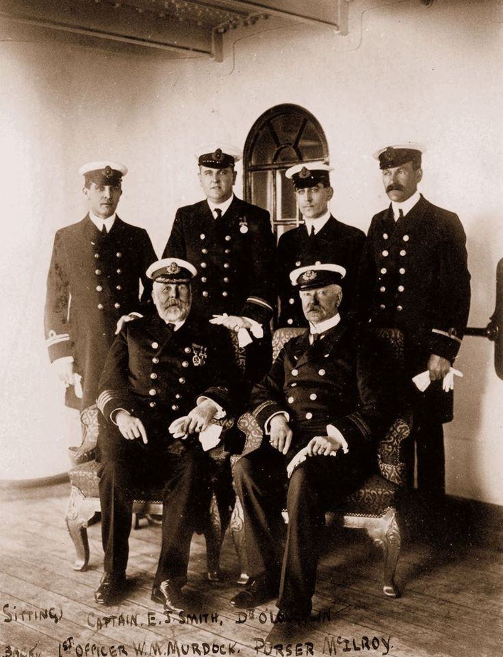 """Променад палубы А на борту """"Олимпика"""" (конец 1911 года). Слева в нижнем ряду сидит капитан Смит. Сверху слева - офицер Уильям Мердок, справа от него - казначей Хью Макэлрой, рядом со Смитом - судовой доктор Уильям О`Лафлин"""